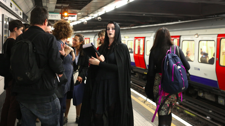 Girl dressed in black goth clothing on a busy tube platform