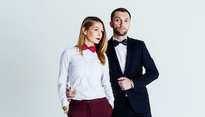 Close up colour studio portrait of stylish young couple, pretty woman and handsome man in a black suit, against plain studio background.
