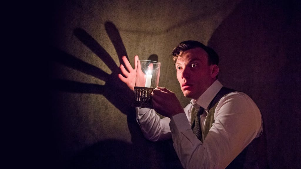 From The Woman in Black, a man holding his hand up to a lantern, creating a large shadow on the wall behind him