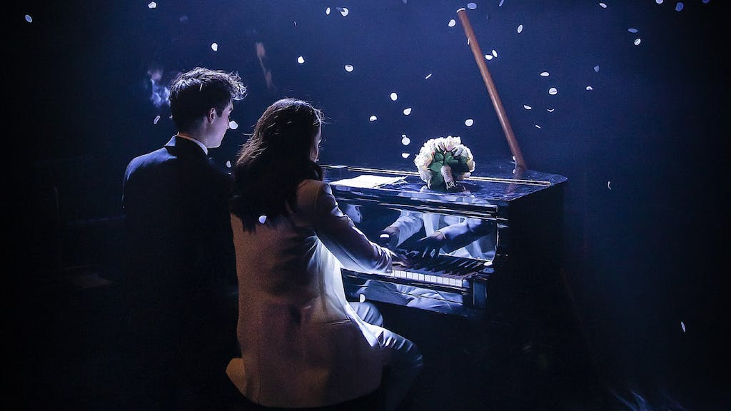 From The Last Five Years, a man and a woman sit at a piano with their backs to the camera. A flower bouquet is on the piano and petals are falling down